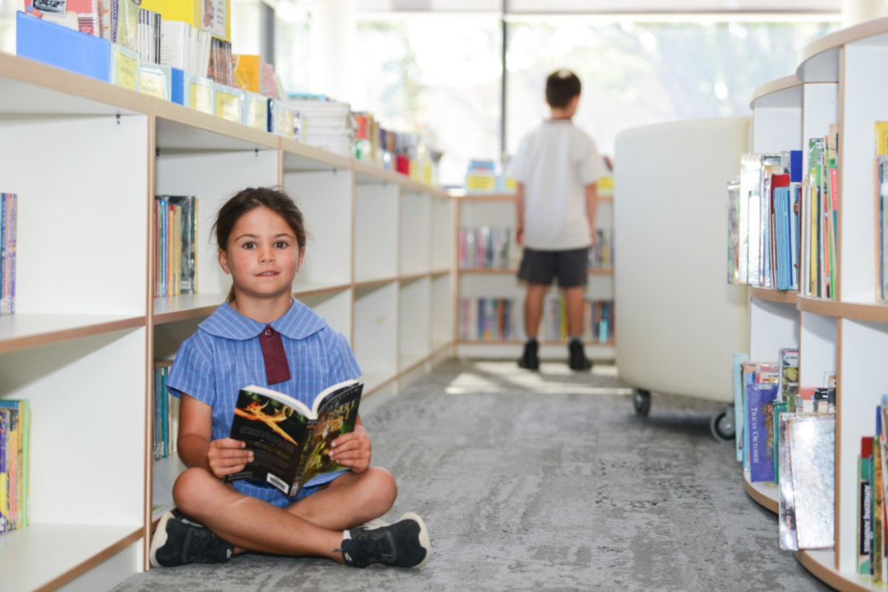 girl sitting on library floor holding a book